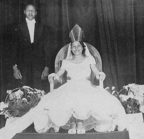 Olavenia Rush, named as first campus queen at Alabama A&M College in 1949, in gown and regalia; male escort standing to her right.