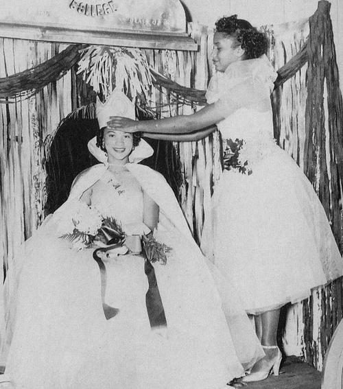 Theresa Powers, named campus queen in 1952, in gown and regalia; being crowned by Miss A&M 1951, Edna Wilson Mullins, standing.