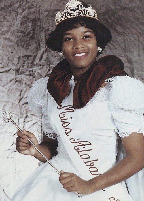 Portrait of Kreslyn Valrie, named campus queen in 1991, in gown and regalia.
