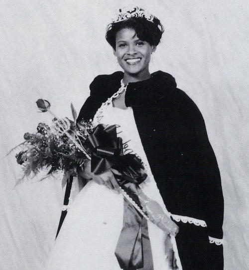 Loretta Wilson, named campus queen in 1995, standing in gown and regalia.
