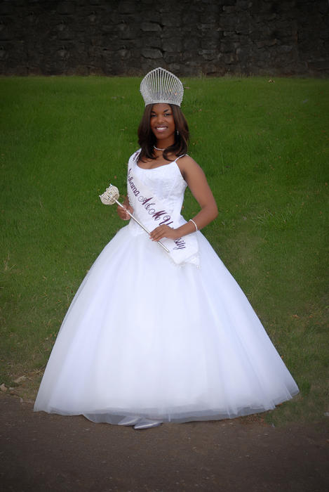 Janine Bates, named campus queen in 2008, standing outdoors in gown and regalia.