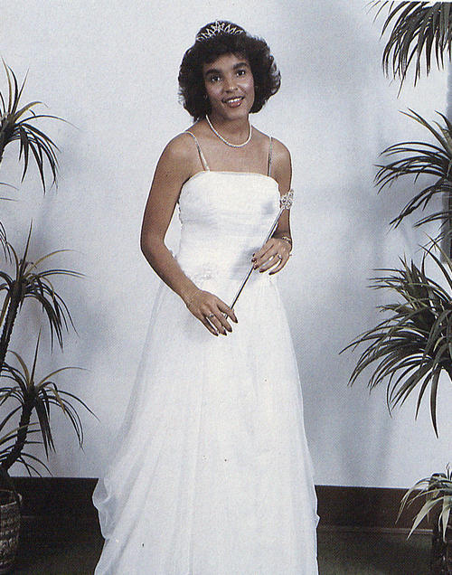 Pamela Williams, named campus queen in 1983, standing in gown and regalia.