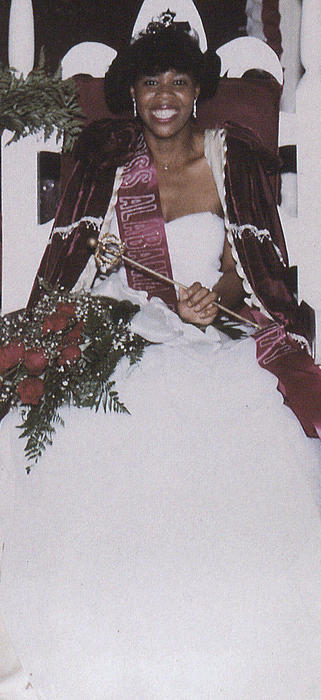 Vera Brewer, named campus queen in 1986, seated in gown and regalia.