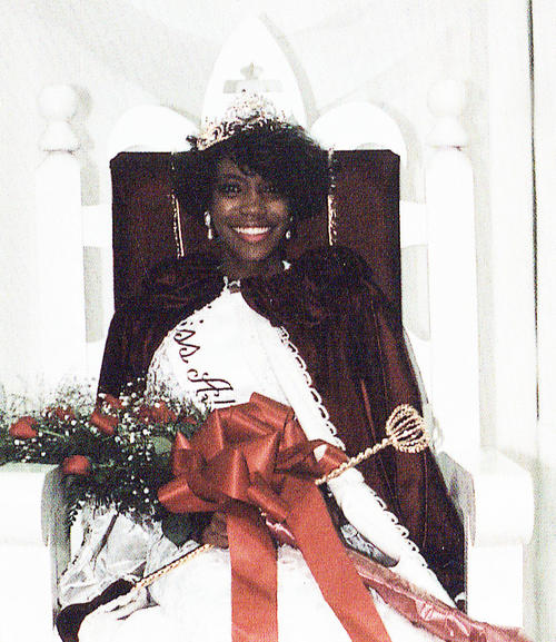 Calandra Raven, named campus queen in 1990, seated in gown and regalia.