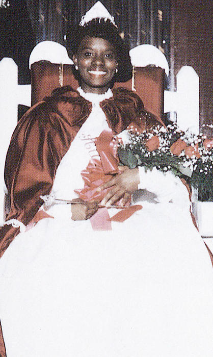 Donna McCullum, named campus queen in 1988, seated in gown and regalia.