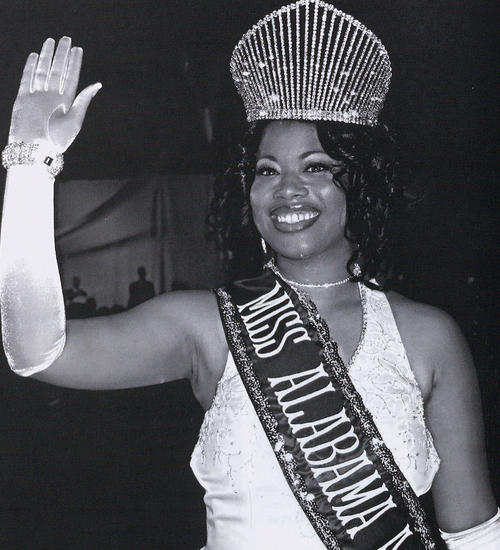Rosina O. England, named campus queen in 2003, in gown and regalia, waving.