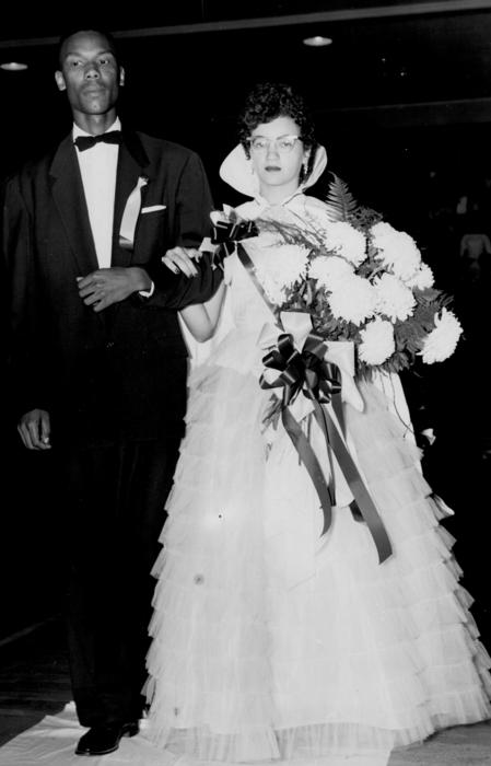 Geneva Stegar, named campus queen in 1956, walking with escort in gown and regalia.