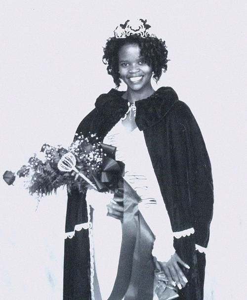 Traci Spann, named campus queen in 1994, standing in gown and regalia.