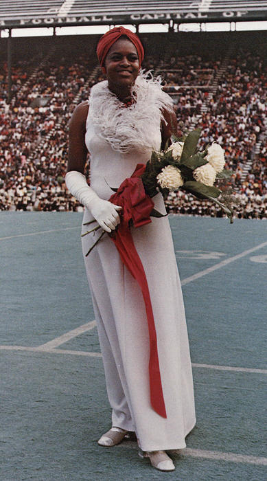 Latricia Perry, named campus queen in 1973, standing on a football field