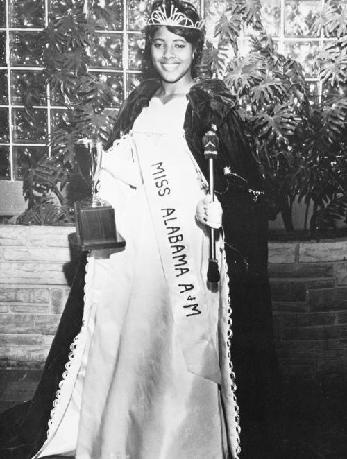 Shirley Faye Oliver, named campus queen in 1964, standing in gown and regalia., Digitized 2014-09 J. F. Drake Memorial LRC, Alabama A&M University.