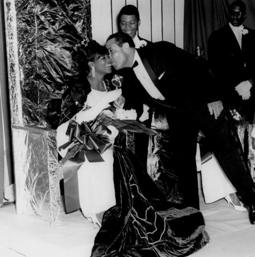 Florastine Williams, named campus queen in 1967 and seated in gown and regalia, recieves a kiss from a young man.