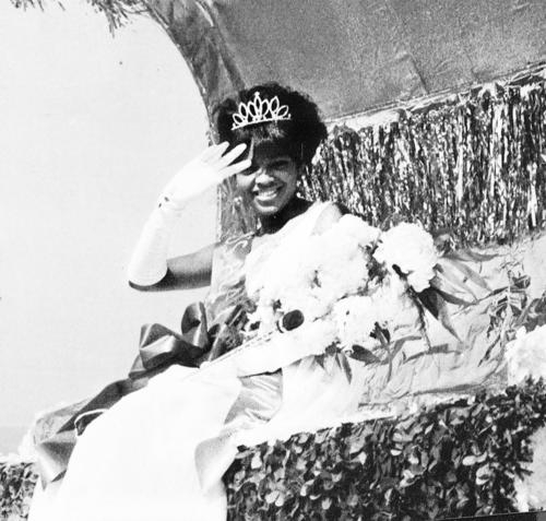 Vivian Jackson, named campus queen in 1969 and seated in gown and regalia, waves to the camera., Digitized 2014-09 J. F. Drake Memorial LRC, Alabama A&M University.