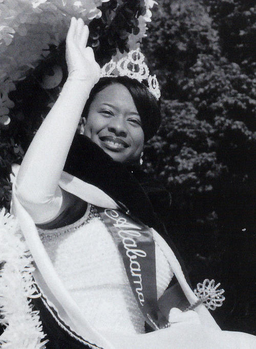 Teneshia Jackson, named campus queen in 1998, seated in gown and regalia, waving to the camera., Digitized 2014-09 J. F. Drake Memorial LRC, Alabama A&M University.