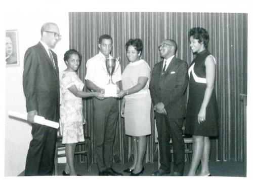 Digitized by J.F. Drake Memorial LRC; Alabama A&M University., President O'Neal and faculty presenting a trophy to Drake State students in the cafetorium.