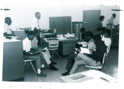 Faculty member teaching college students in class.  A typewriter is visible on the center desk., Digitized by J.F. Drake Memorial LRC; Alabama A&M University.