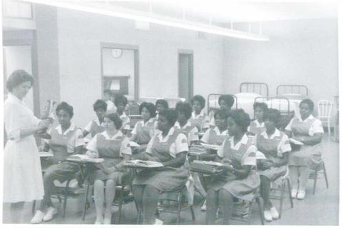 Nursing faculty teaching a class of female nursing students with two beds in the background., Digitized by J.F. Drake Memorial LRC; Alabama A&M University.